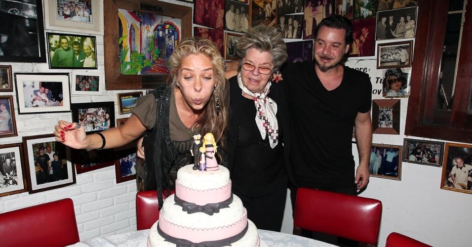 Adriane Galisteu assopra as velinhas ao lado do marido, Alexandre Iódice, e da mãe, Emma, em um restaurante na cidade de São Paulo (18/4/12)