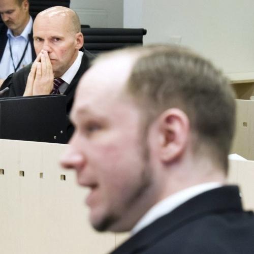 Anders Breivik, autor do massacre de julho de 2011 na Noruega, fala à corte no quarto dia de seu julgamento (ao fundo, seu advogado, Geir Lippestad). Devido a reclamações de familiares das vítimas, o assassino confesso não fez sua saudação de extrema direita ao chegar ao tribunal, diferentemente de outros dias