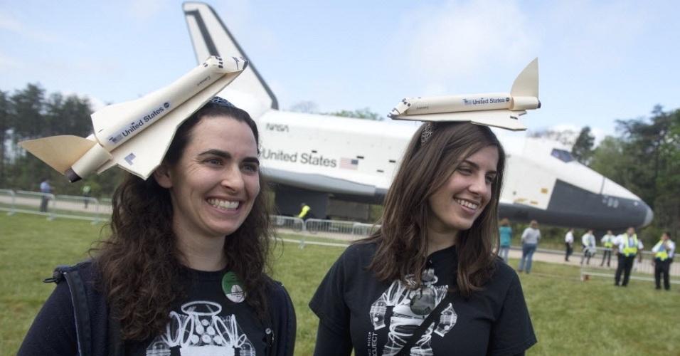 Funcionárias do Smithsonian Institute enfeitam cabeças com réplicas do ônibus espacial Discovery, tendo ao fundo a nave, que fez sua última viagem e virou peça de museu