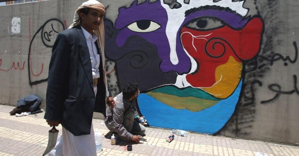 Homem com adaga caminha ao lado de voluntário pintando muro em Sanaa, capital do Iêmen