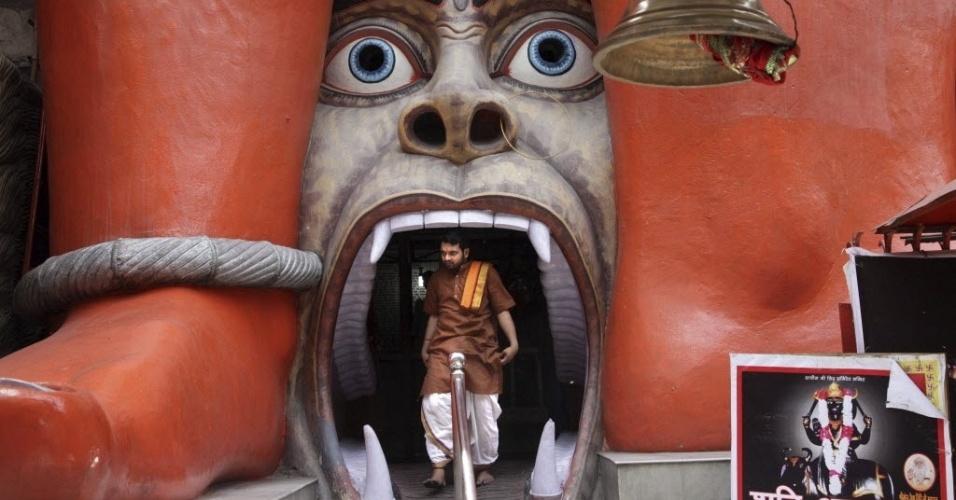 Homem de Nova Délhi (Índia) sai do templo do deus Hanumán, divindade hindu metade humana e metade macaco