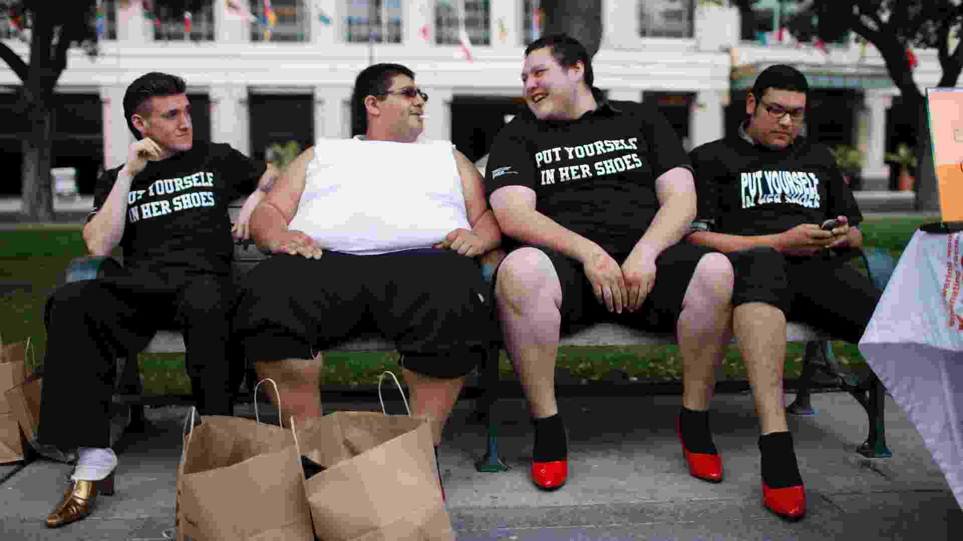 """Stephen Lam/Reuters - Homens com sapatos de salto descansam em bancos durante o evento anual """"Caminhe uma milha com os sapatos dela"""", para aumentar a conscientização contra a violência sexual em San José, na Califórnia (EUA)"""