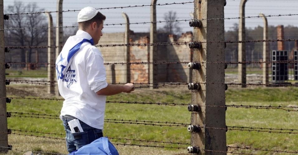 """Jovem se ajoelha em  campo de exterminio de Auschwitz, na Polonia. Os judeus realizam a 21ª """"Marcha dos Vivos"""", celebração anual que lembra os horrores do Holocausto"""