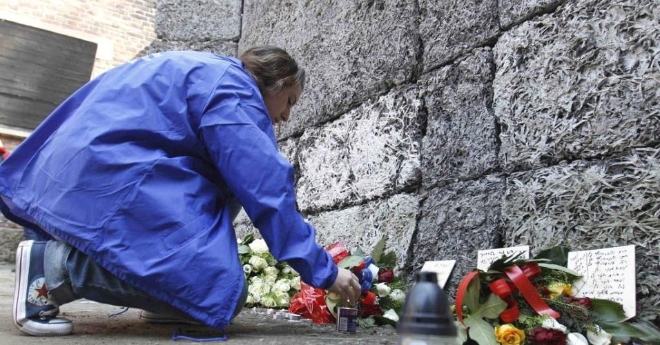 """Menina acende vela em muro no antigo campo nazista de Auschwitz, ao sul da Polônia, durante a 21ª """"Marcha dos Vivos"""", celebração anual que lembra os horrores do Holocausto"""