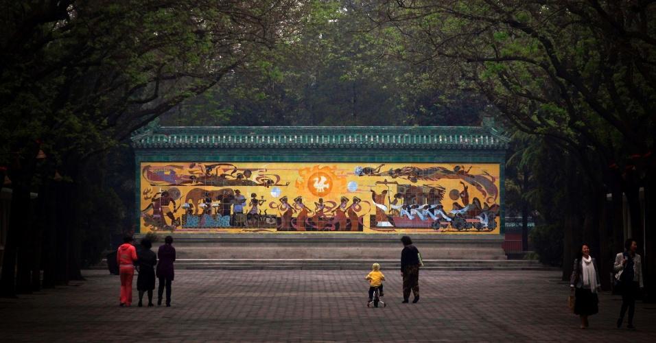 Menina pedala em frente a muro pintado próximo ao Templo do Sol, em Pequim, na China
