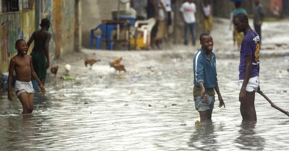 Moradores andam por área alagada em Kinshasa, no Congo