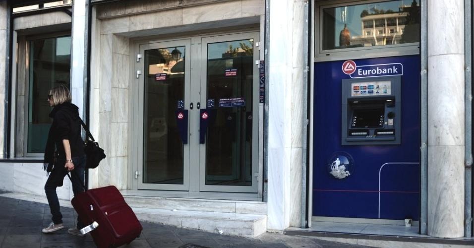 Mulher com mala passa em frente a banco em Atenas, capital da Grécia. Os quatro maiores bancos do país se preparam para anunciar na sexta-feira (20) grandes prejuízos, em função da reestruturação da dívida grega