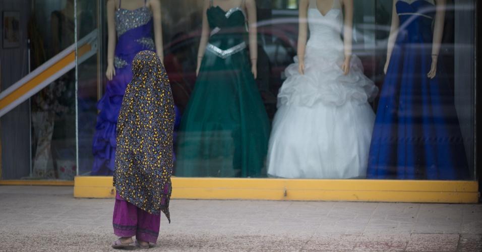 Mulher usando véu observa loja de roupas femininas em Cabul, no Afeganistão