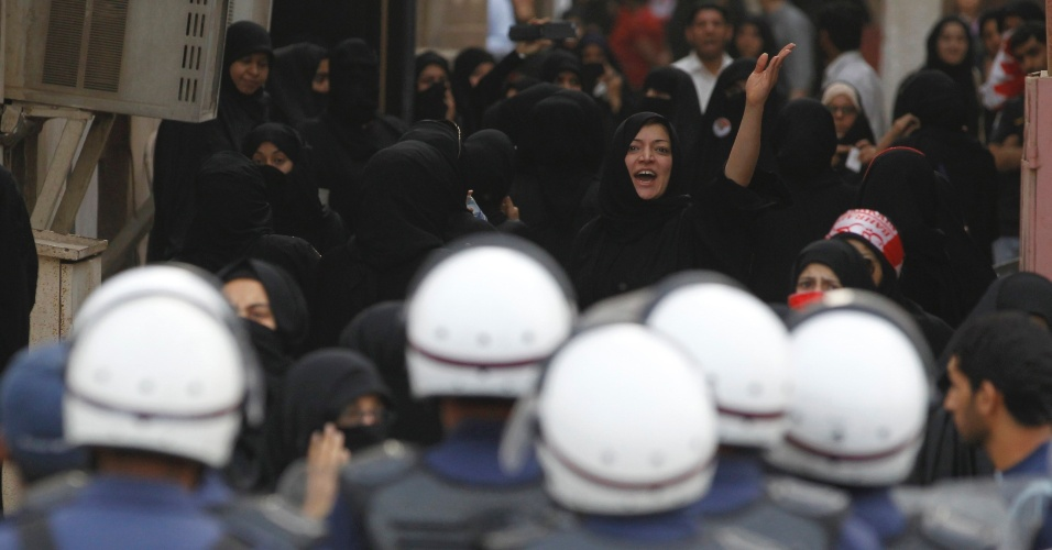Mulheres observam policiais durante protesto nesta quinta-feira em Manama, no Bahrein, contra o governo do país