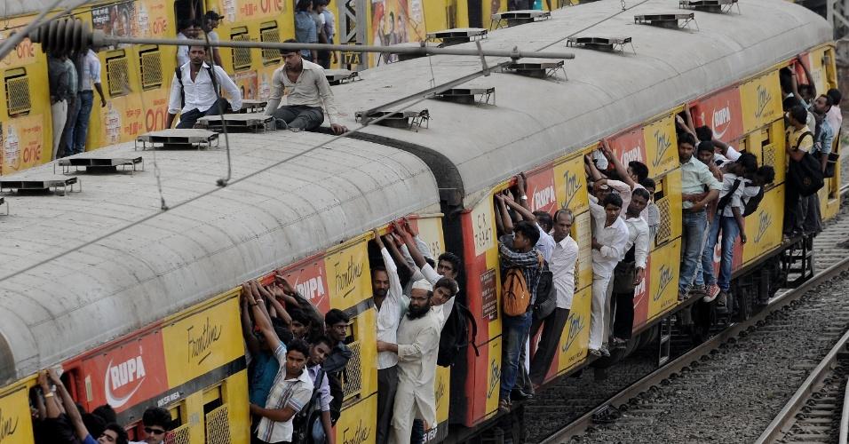 Passageiros se penduram em portas de trem superlotado em Mumbai, na Índia