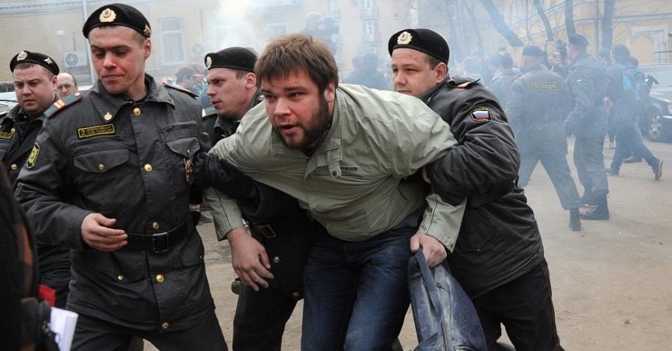 """Policiais detêm manifestante do lado de fora de corte em Moscou, capital russa. O protesto é contra o governo e em favor da banda punk Pussy Riot, que teve três de suas integrantes presas há dois meses, após a banda escalar a catedral da igreja moscovita e cantar uma música chamada """"Punk prayer"""" (prece punk, em inglês). As integrantes presas foram acusadas de hooliganismo cometido por um grupo organizado, acusação considerada grave"""