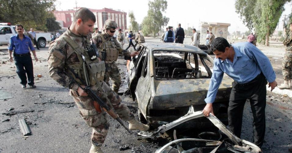 Seguranças curdos inspecionam local onde carro-bomba explodiu em Kirkuk, no Iraque