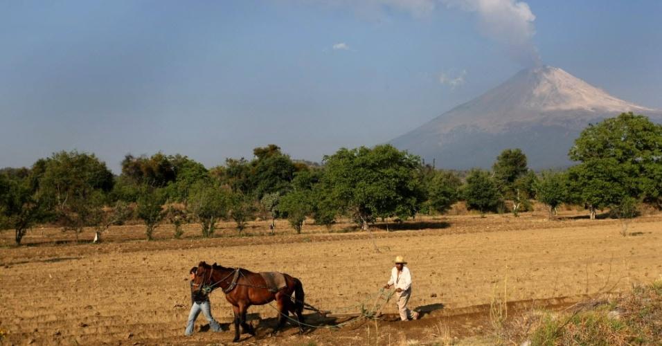 Trabalhadores rurais são vistos em  San Nicolás de Los Ranchos, em Puebla (México), perto do vulcão Popocatépetl, que emitou cinzas nas últimas horas