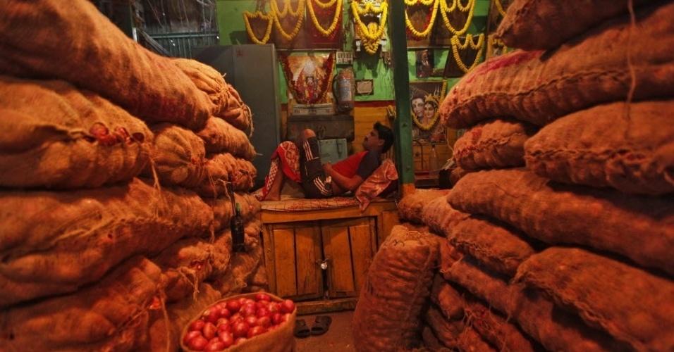 Vendedor descansa próximo em comércio de verduras e legumes em mercado de Kolkata, na Índia