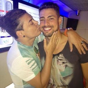 David Brazil dá um beijo em Cauã Reymond durante a gravação de um programa de rádio.