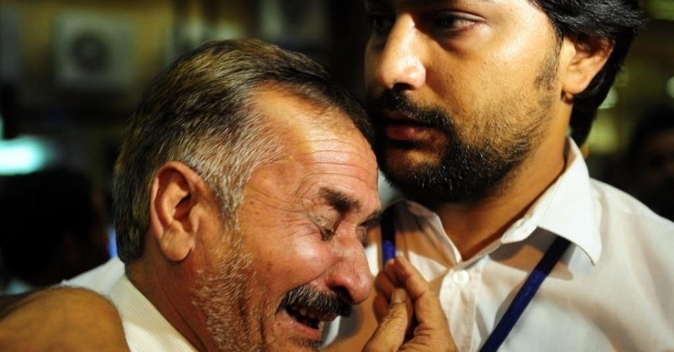 Familiares de um dos passageiros do avião da Bhoja Airline, que caiu nesta sexta-feira (20), se consolam no aeroporto de Karachi, Paquistão