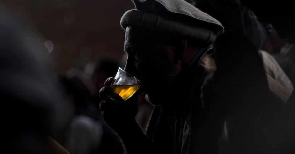Homem bebe chá durante rinha de galos em Cabul, no Afeganistão
