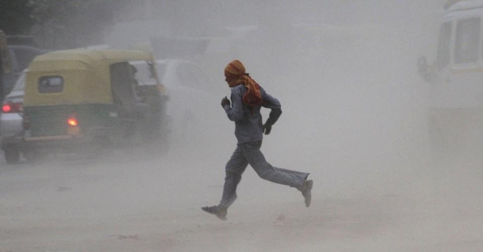 Homem corre em estrada para se proteger de tempestade de areia em Noida, periferia de Nova Délhi, capital da Índia