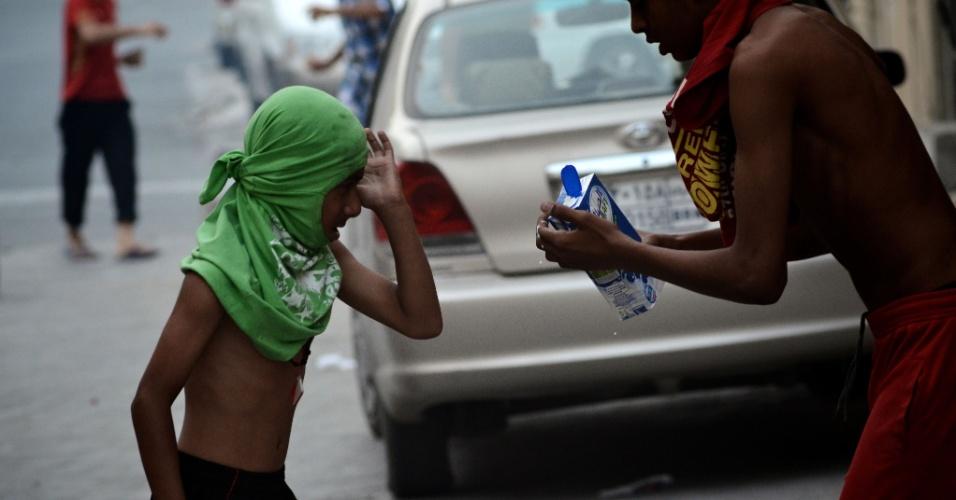 Jovem bareinita usa leite para proteger os olhos de um garoto dos efeitos de bombas de gás lacrimogênio durante protestos em Manama, capital do Bahrein. Os manifestantes se opõem à realização do GP de Fórmula 1 no país