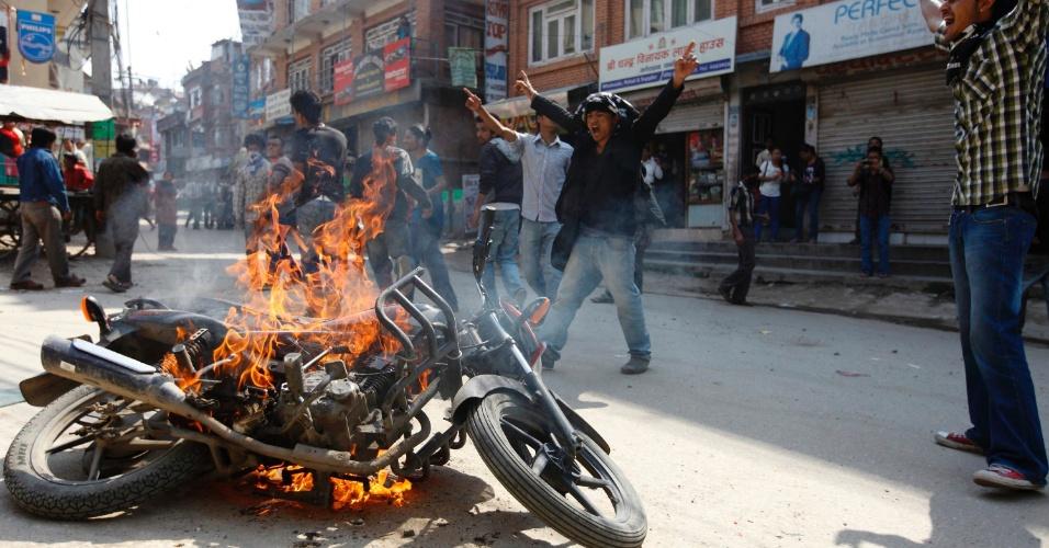 Jovens da União de Estudantes do Nepal incendeiam motocicleta pertencente ao governo em protesto em Katmandú, no Nepal