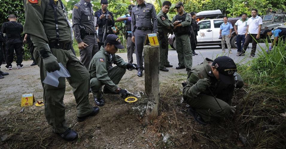 Membros do esquadrão antibombas tailandês inspecionam rodovia após ataque a bomba realizado por militantes separatistas na província de Narathiwat, na Tailândia