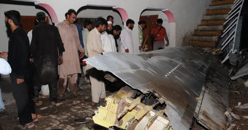 População observa destroços do Boeing 737 que caiu perto do aeroporto internacional de Rawalpindi, cidade próxima à capital Islamabad, no Paquistão, nesta sexta-feira (20)