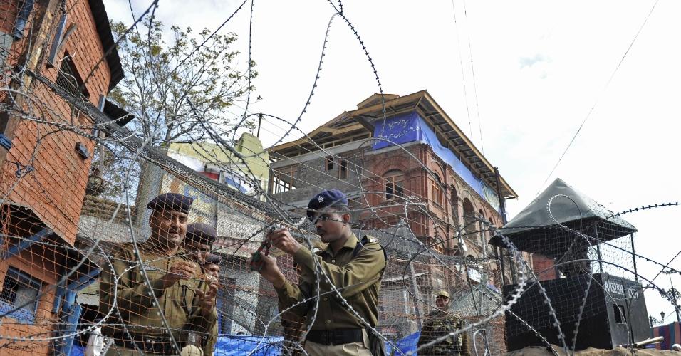 Soldados indianos cortam cerca de arame farpado durante processo de demolição de bunker em Srinagar, na Índia