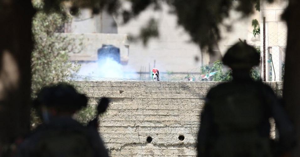Soldados israelenses observam palestino mascarado durante confrontos no vilarejo de Nabi Salah, na região da Cisjordânia. Os manifestantes palestinos protestam contra a construção de assentamentos judaicos no território palestino
