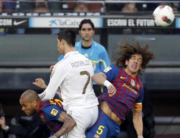 Cristiano Ronaldo divide lance com o brasileiro Daniel Alves (e) e o capitão do Barcelona Carles Puyol (d)
