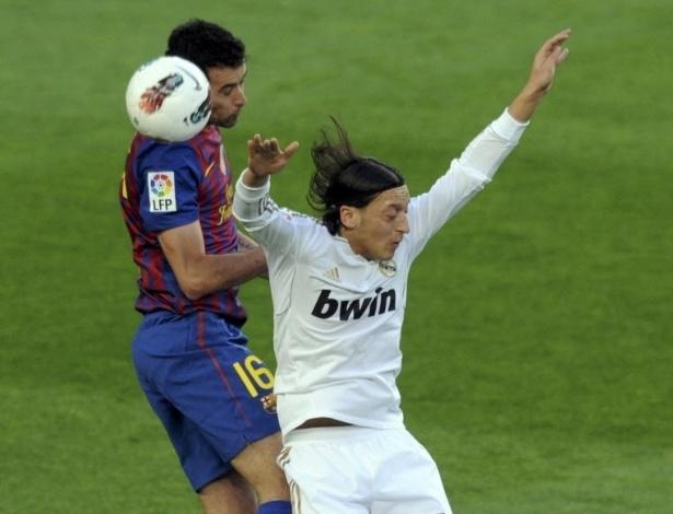 Meia alemão do Real Madrid, Özil sobe junto com o volante do Barcelona, Sergio Busquets, para ganhar o lance