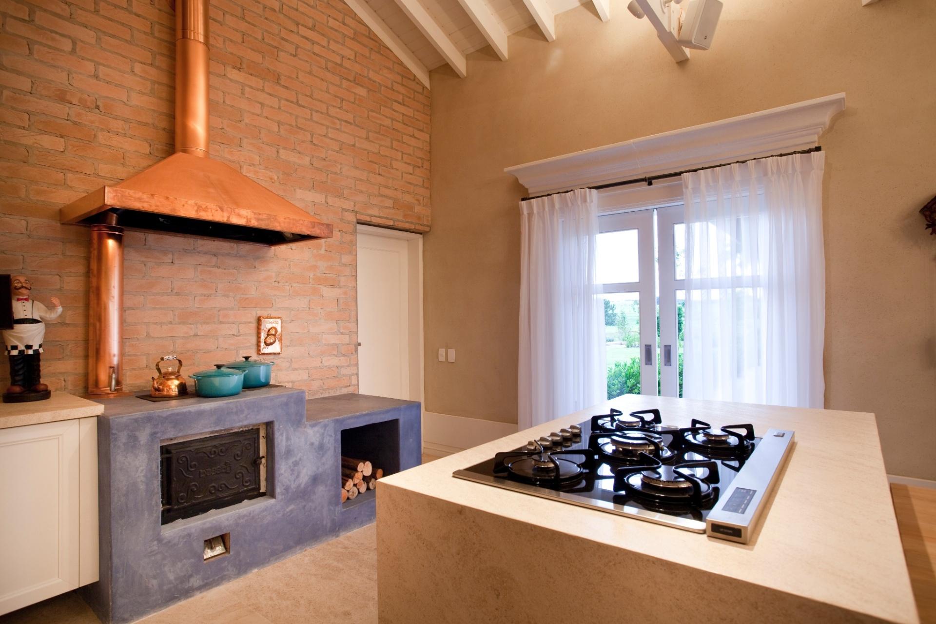 Junto à mesa Micasa, o volume de Limestone Mont Dorê (Pedras de Esquina Marmoraria) com cooktop. Ao fundo, o fogão à lenha da cozinha gourmet também serve, no inverno, para aquecer os ambientes sociais. O projeto no interior de SP é de Maurício Karam