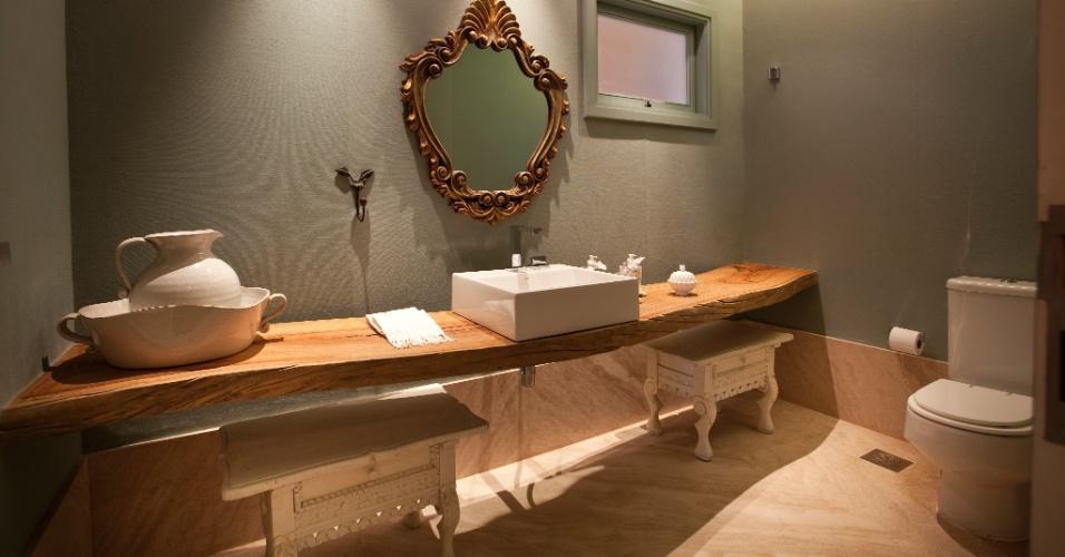No lavabo, a base para cuba, Deca, é feita de tronco de madeira encerado, enquanto as paredes estão revestidas com linho verde. Espelho e criados-mudos são antigos e garimpados em feiras de rua, no interior de SP. O projeto é de Maurício Karam