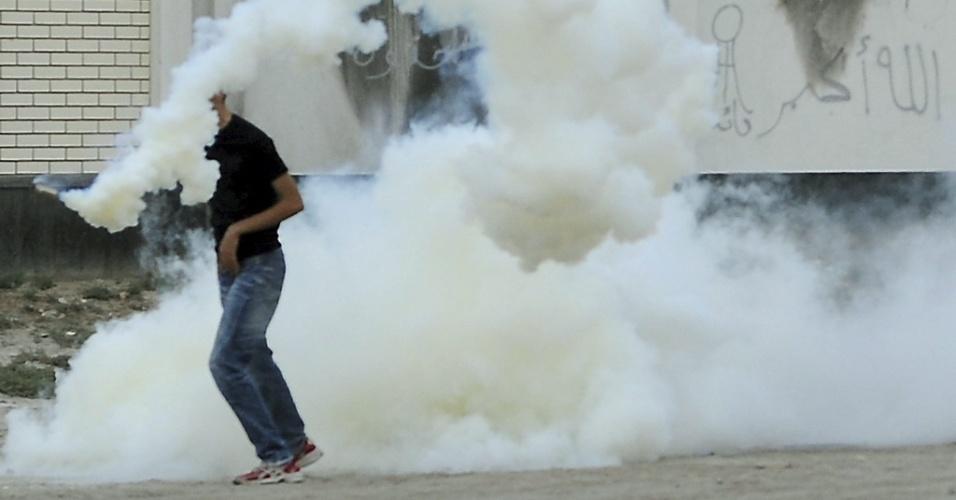 Ativista antigoverno é envolvido pela fumaça de uma bomba de gás lacrimogênio em Bilad Al-Qadeem, no Bahrein