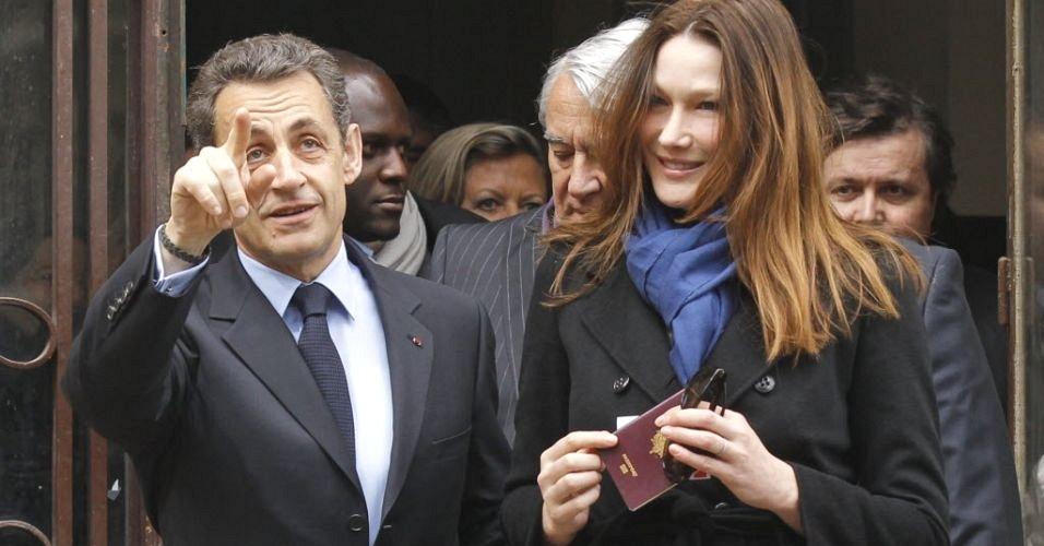 Atual presidente da França e candidato à reeleição, Nicolas Sarkozy, deixa zona eleitoral após votar no 1° turno da disputa, neste domingo (22) acompanhado da primeira-dama, Carla Bruni