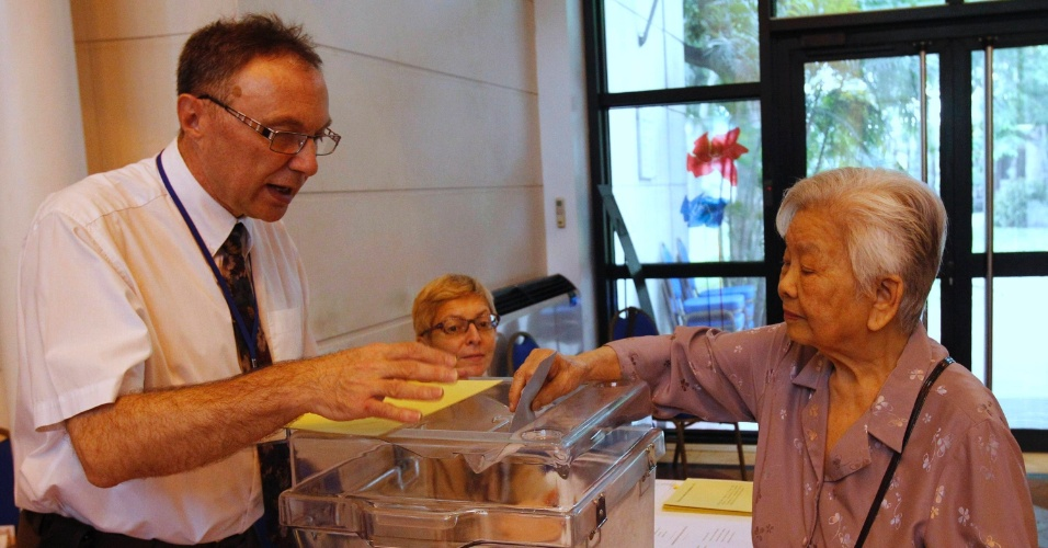 Francesa com ascendência vietnamita lança seu voto durante eleição presidencial francesa, neste domingo (22), em Hanói, capital do Vietnã.  Cerca de 1,4 mil eleitores são esperados para votar na Embaixada da França no Vietnã