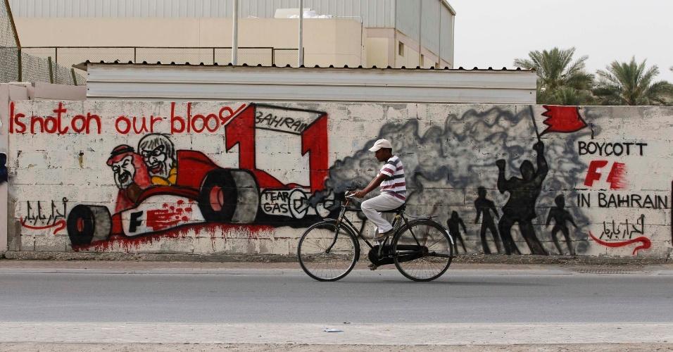 Homem anda de bicicleta na aldeia de Diraz, a oeste de Manama, capital do Bahrein, e passa por muro com pichações de manifestantes contra a realização do GP do Bahrein de Fórmula 1, que acontece neste domingo (22), no circuito de Sakhir. Pelo segundo dia consecutivo, foram registrados confrontos entre manifestantes e policiais em várias cidades do país, antes do início do evento. Como forma de protestar contra o governo, os rebeldes exigem a suspensão do GP