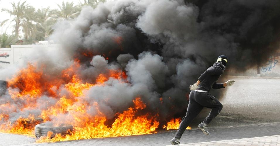 Manifestante corre para se proteger após queimar pneus em Budaiya, a oeste de Manana