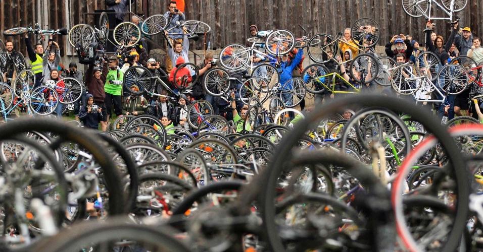 Milhares de ciclistas seguram ao alto suas bicicletas em Budapeste, durante um passeio ciclístico em comemoração ao Dia da Terra