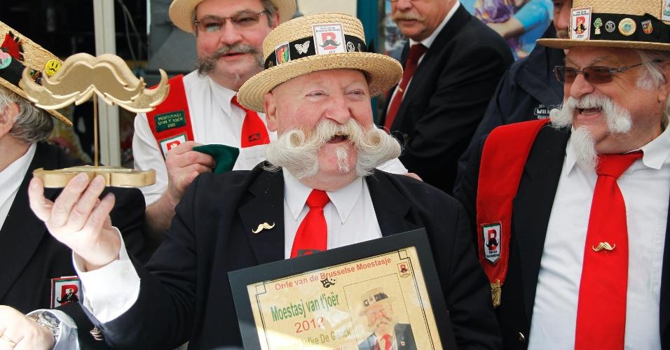 O simpático bigodudo Jef (centro) segura orgulhosamente seu troféu depois de ganhar a disputa do Melhor Bigode de 2012 em Bruxelas, Bélgica