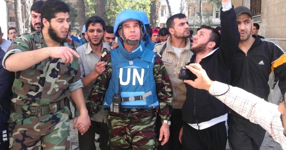 Oposicionistas da Síria acompanham o coronel Ahmed Himmiche (centro), observador da ONU, durante visita à cidade de Homs, uma das mais atingidas pela repressão do regime