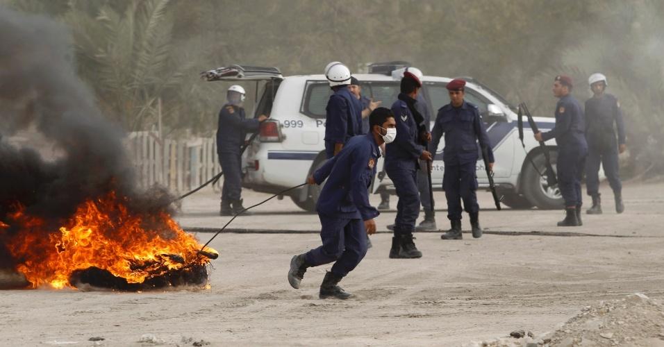 Policial arrasta barricada durante confrontos em Manama