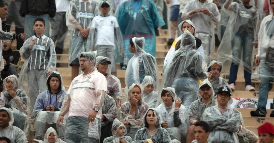 Torcedores corintianos usam capas de plástico para se protegerem da chuva