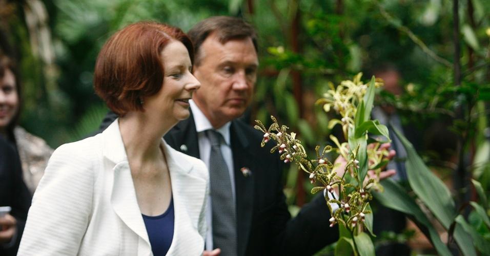 A primeira-ministra australiana, Julia Gillard, cheira orquídea após cerimônia de nomeação das flores nos Jardins Botânicos de Cingapura