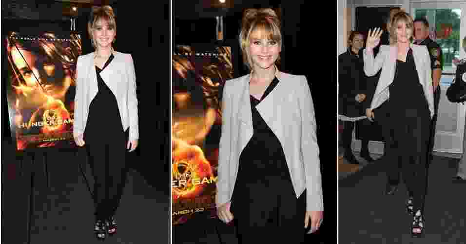 """Jennifer Lawrence, do filme """"Jogos Vorazes"""", investe em um estilo básico com detalhes ou peças que contam com um toque diferente. Para o dia-a-dia, a atriz costuma usar calça e blazer, como o look preto com bege, usado para divulgar o filme em Plantation, na Florida, Estados Unidos. O blazer de corte seco e geométrico Elie Saab traz formalidade à combinação de calça levemente saruel da fast-fashion H&M e blusa de modelagem torcida da Helmut Lang (08/03/2012) - Getty Images"""