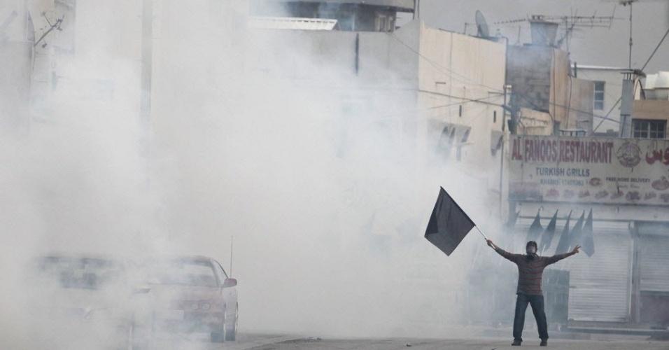 Manifestante agita bandeira preta no Bahrein, durante confrontos entre a polícia e a população na capital bareinita, Manama. Os protestos mais recentes tiveram início no fim de semana, às vésperas do GP de F-1 no país, e deixaram pelo menos um morto