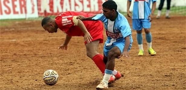 Jogador do Galo do Parque (vermelho) sofre falta, na derrota para o Leões da Geolândia (azul)