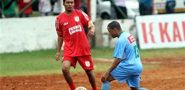 Jogador do Leões da Geolândia (azul) tenta finta, na vitória sobre o Galo do Parque (vermelho)