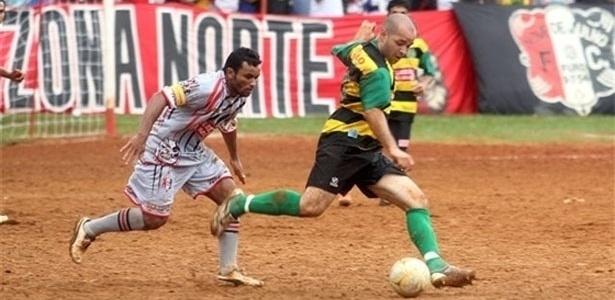 Jogador do Nove de Julho (cinza) se prepara para chutar, na derrota para o Lagoinha (amarelo e preto)