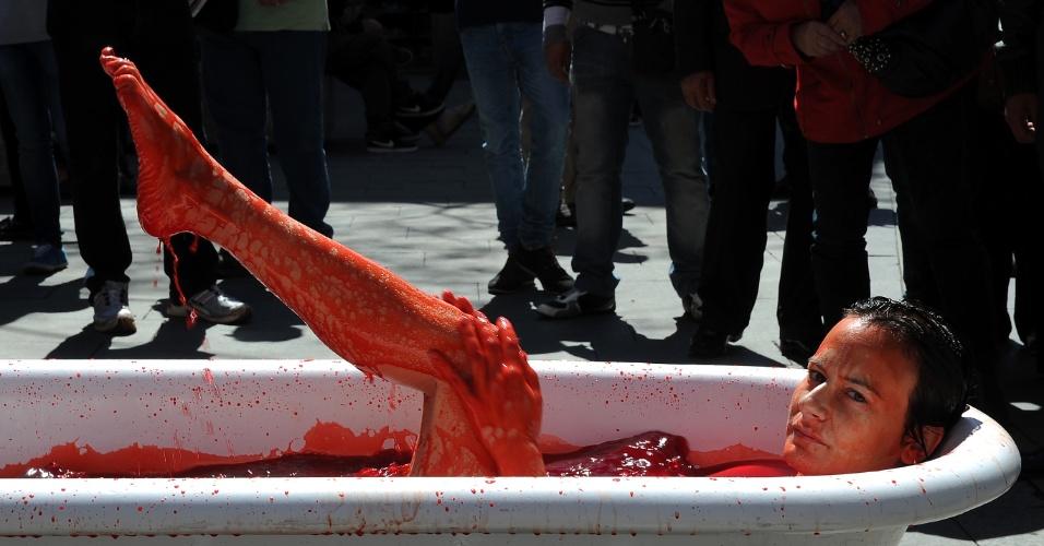 Para protestar contra o uso de animais pela indústria de cosméticos, ativista da organização internacional AnimaNaturalis simula tomar banho em banheira cheia de sangue no centro de Barcelona, na Espanha