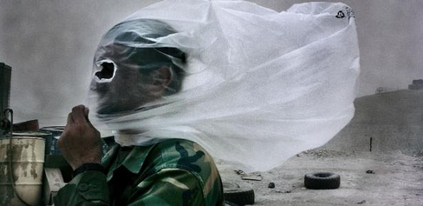 A foto ícone do trabalho de Balazs mostra um soldado afegão com um saco plástico na cabeça durante tempestade de areia causada por um combate (28/10/2010)  - BalazsGardi/Basetrack.org